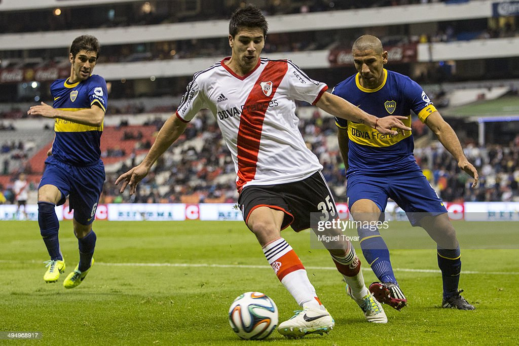 Daniel Diaz of Boca defends as Giovanni Simeone of River drives the ball during a friendly match between Boca Juniors and River Plate at Azteca Stadium on May 31, 2014 in Mexico City, Mexico.
