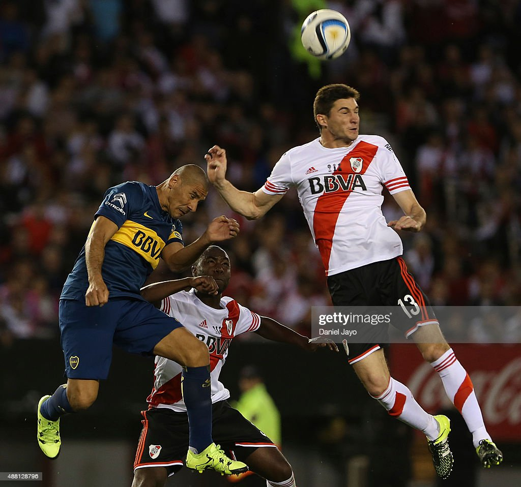 Daniel Diaz, of Boca Juniors, (L) and Lucas Alario, of River Plate, go for a header during a match between River Plate and Boca Juniors as part of 24th round of Torneo Primera Division 2015 at Monumental Antonio Vespucio Liberti Stadium on September 13, 2015 in Buenos Aires, Argentina.
