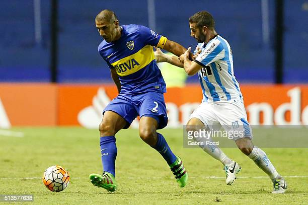 Daniel Diaz of Boca Juniors fights for the ball with Lisandro Lopez of Racing Club during a group stage match between Boca Juniors and Racing Club as...