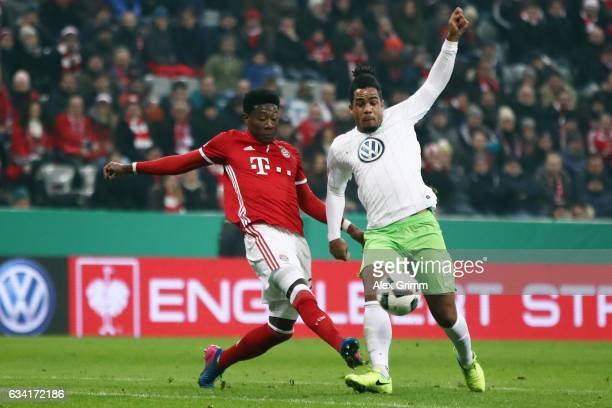 Daniel Didavi of Wolfsburg is challenged by David Alaba of Muenchen during the DFB Cup Round Of 16 match between Bayern Muenchen and VfL Wolfsburg at...