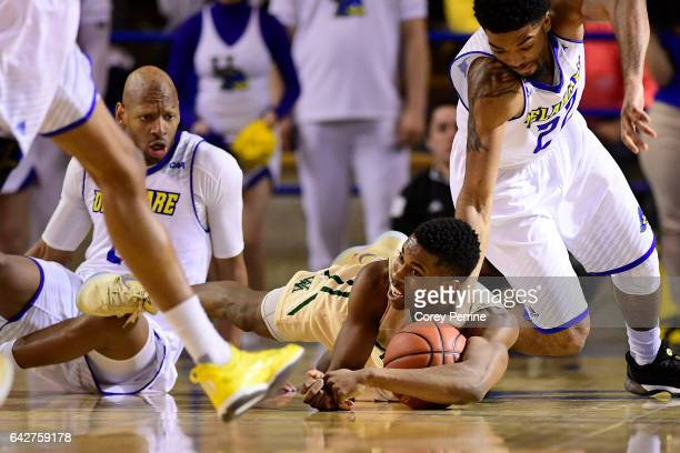 Daniel Dixon of the William Mary Tribe corrals a loose ball as Barnett Harris looks on and Cazmon Hayes of the Delaware Fightin Blue Hens tries to...