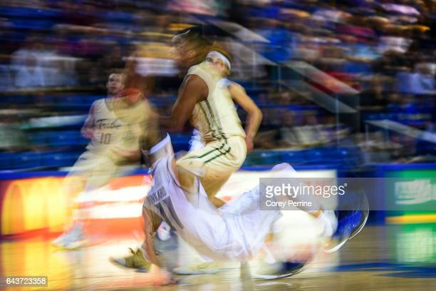 Daniel Dixon of the William Mary Tribe drives as Devonne Pinkard of the Delaware Fightin Blue Hens is called on the defensive foul during the second...