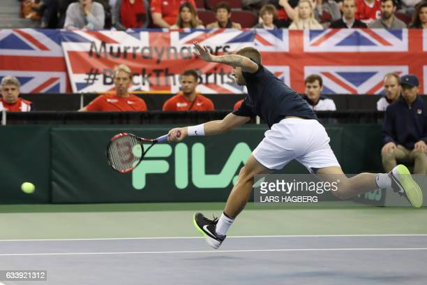 Daniel Evans of Great Britain hits a return in the first set against Vasek Pospisil of Canada the third day of Davis Cup first round between Canada...
