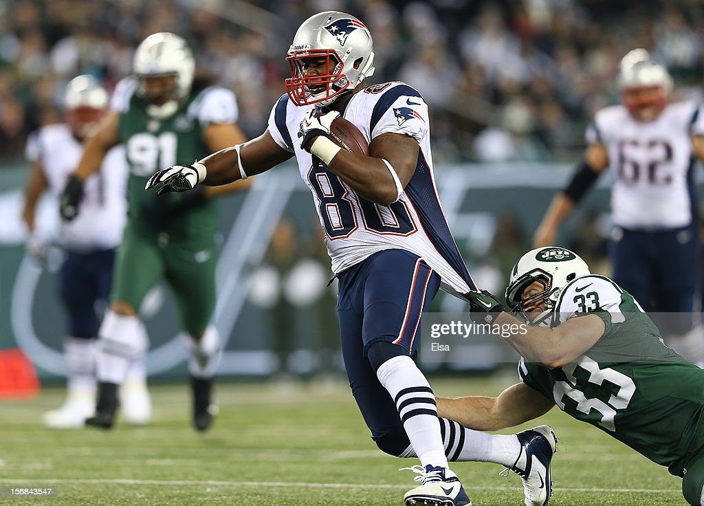 Daniel Fells #86 of the New England Patriots carries the ball as Eric Smith #33 of the New York Jets defends on November 22, 2012 at MetLife Stadium in East Rutherford, New Jersey.The New England Patriots defeated the New York Jets 49-19.