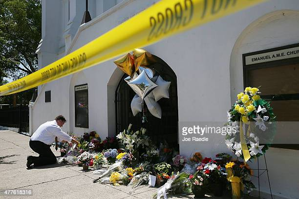 Daniel Flessas lays flowers in front of Emanuel AME Church on June 18 2015 in Charleston South Carolina Nine people were killed on June 17 in a mass...