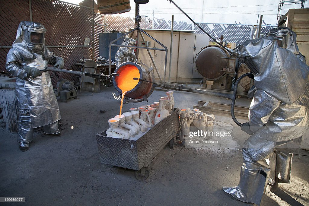 Daniel Flores, Adalid Orozco, Jose Sosa and Enrique Guerrero pour molten bronze metal into molds at the casting of the Screen Actors Guild Award statuettes, at the American Fine Arts Foundry on January 17, 2013 in Burbank, California.