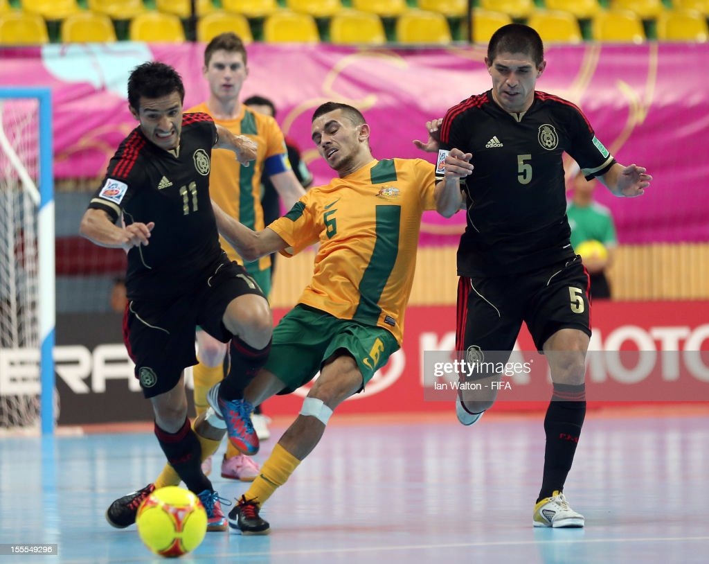Daniel Fogarty of Australia is tackled by Morgan Plata of Mexico during the FIFA Futsal World Cup Thailand 2012, Group D match between Australia and Mexico at Nimibutr Stadium on November 5, 2012 in Bangkok, Thailand.