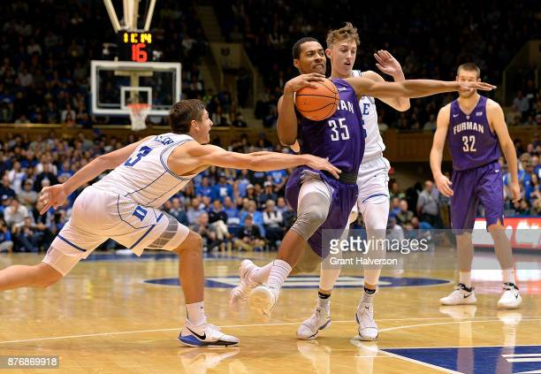 Daniel Fowler of the Furman Paladins drives between Grayson Allen and Alex O'Connell of the Duke Blue Devils during their game at Cameron Indoor...