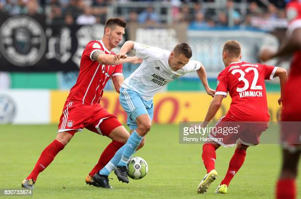 Daniel Frahn of Cottbus vies with Niklas Suele and Joshua Kimmich of Muenchen during the DFB Cup first round match between Chemnitzer FC and FC...