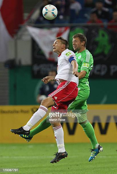 Daniel Frahn of Leipzig and Marco Russ of Wolfsburg head for the ball during the DFB Cup first round match between RB Leipzig and VfL Wolfsburg at...
