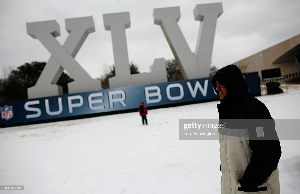 Daniel Garza (L) watches as his son, Robert Garza, 10, walks through snow and ice while visiting an NFL Super Bowl XLV display February 1, 2011 in Dallas, Texas. A major ice storm hit the Dallas/Fort Worth area overnight days before Super Bowl XLV is to be held in Arlington, Texas.