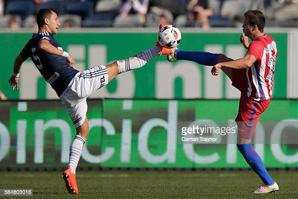 Daniel Georgievski of the Victory and Javier Manquillo of Atletico Madrid compete for the ball during the match between Melbourne Victory and...