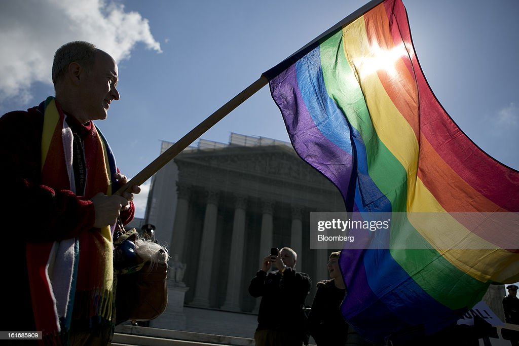 Daniel German Domingues from Massachusetts holds a rainbow flag while demonstrating outside the U.S. Supreme Court in Washington, D.C., U.S., on Tuesday, March 26, 2013. The Supreme Court takes up what is probably its biggest civil-rights dispute in decades this week when it hears arguments that could lead to the legalization of same-sex marriage nationwide. Photographer: Andrew Harrer/Bloomberg via Getty Images