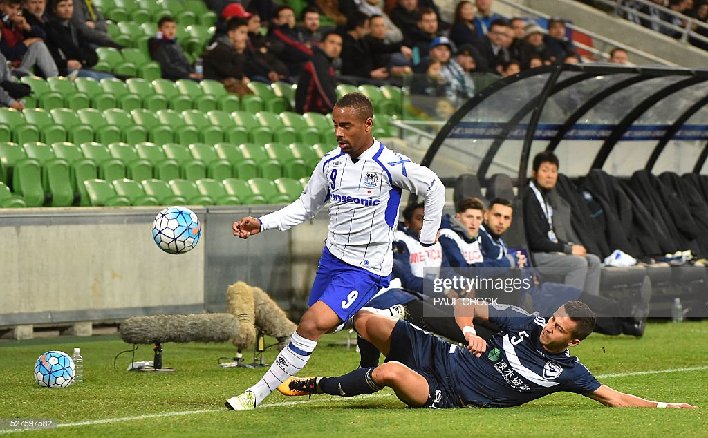 Daniel Gerogievski (R) of Melbourne Victory tackles Ademilson (L) of Gamba Osaka during the AFC Champions League football match between Melbourne Victory and Gamba Osaka in Melbourne on May 3, 2016. / AFP / Paul Crock / IMAGE