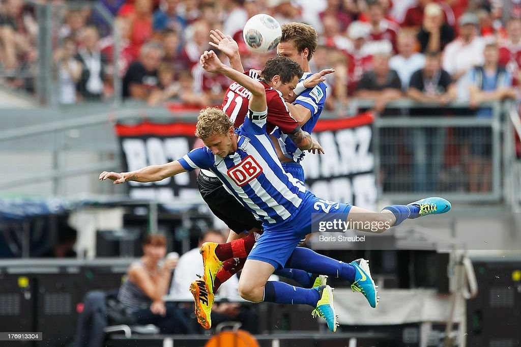 Daniel Ginczek (C) of Nuernberg jumps for a header with Fabian Lustenberger (L) and <a gi-track='captionPersonalityLinkClicked' href=/galleries/search?phrase=Sebastian+Langkamp&family=editorial&specificpeople=808587 ng-click='$event.stopPropagation()'>Sebastian Langkamp</a> (R) of Berlin during the Bundesliga match between 1. FC Nuernberg and Hertha BSC Berlin at Grundig Stadium on August 18, 2013 in Nuremberg, Germany.
