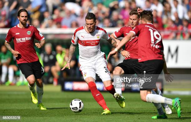 Daniel Ginczek of Stuttgart is challenged by Florian Hbner and Waldemar Anton of Hannover during the Second Bundesliga match between Hannover 96 and...
