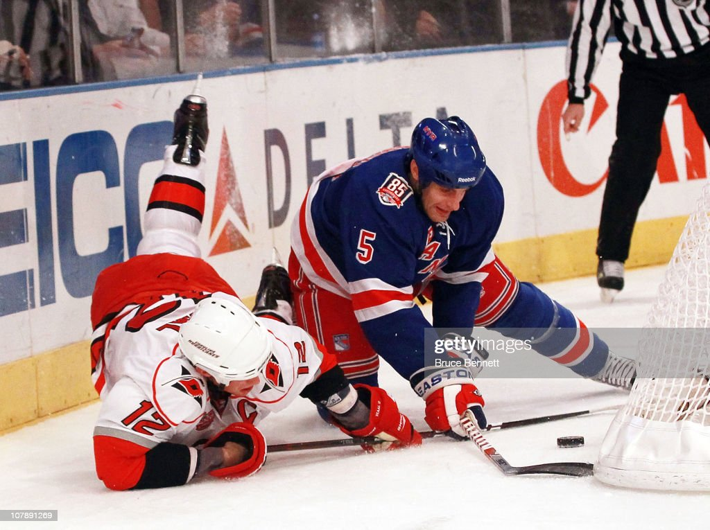 Daniel Girardi of the New York Rangers and Eric Staal of the Carolina Hurricanes battle for the puck at Madison Square Garden on January 5 2011 in...