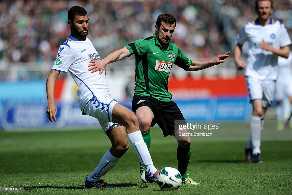 Daniel Gordon (L) of Karlsruhe and Matthew Taylor (R) of Muenster battle for the ball during the 3. Liga match between Preussen Muenster and Karlsruher SC at Preussenstadion on April 20, 2013 in Muenster, Germany.