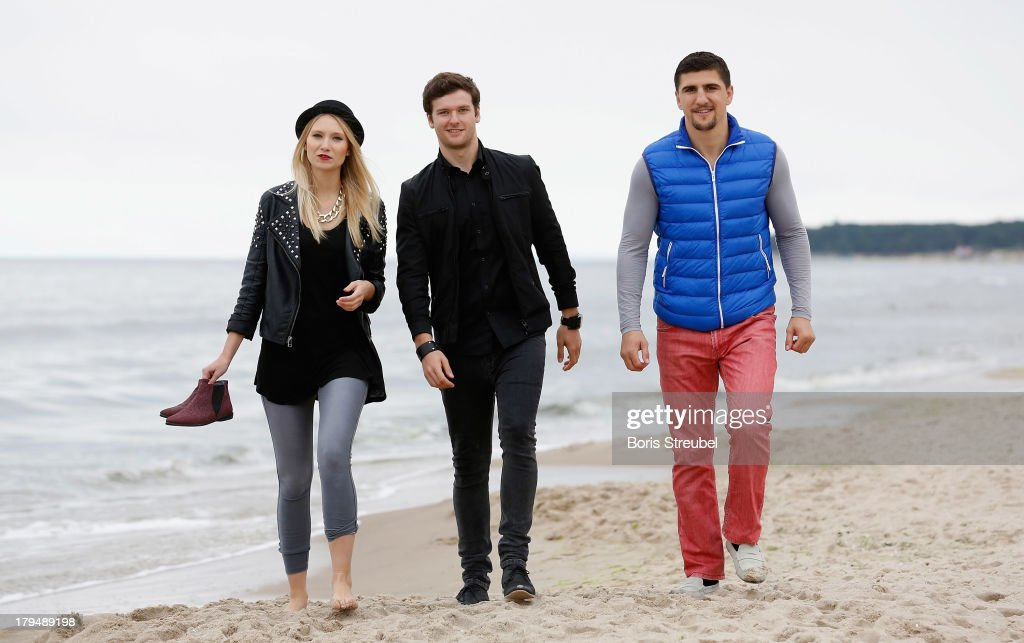 Daniel Grunenberg (C) and Carolin Niemczyk (L) of the pop band Glasperlenspiel walk on the beach of Usedom with WBO Cruiserweight champion <a gi-track='captionPersonalityLinkClicked' href=/galleries/search?phrase=Marco+Huck&family=editorial&specificpeople=2264905 ng-click='$event.stopPropagation()'>Marco Huck</a> (R) of Germany on September 4, 2013 in Zinnowitz, Germany.