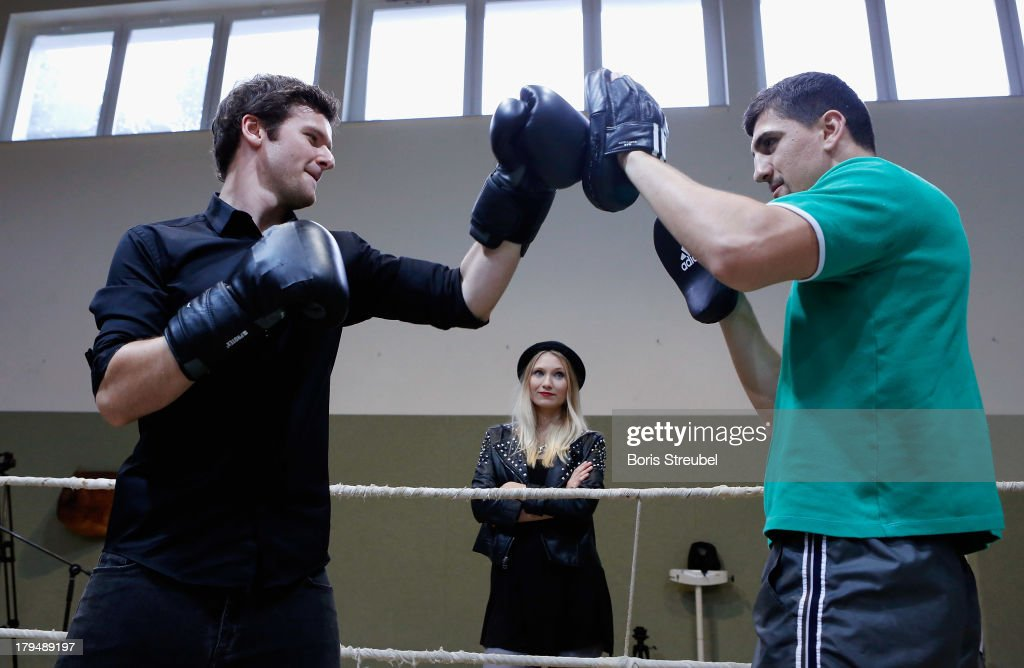 Daniel Grunenberg (L) of the pop band Glasperlenspiel in action against WBO Cruiserweight champion <a gi-track='captionPersonalityLinkClicked' href=/galleries/search?phrase=Marco+Huck&family=editorial&specificpeople=2264905 ng-click='$event.stopPropagation()'>Marco Huck</a> (R) of Germany in the ring of his training camp on Usedom on September 4, 2013 in Zinnowitz, Germany.