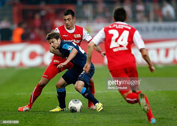 Daniel Halfar of Koeln is challenged by Roberto Puncec and Steven Skrzybski of Union Berlin during the Second Bundesliga match between 1FC Union...