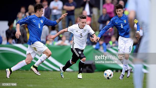 Daniel Haritonov of Germany is challenged by Fabrizio Caligara and Davide Battella of Italy during the U16 international friendly match between...