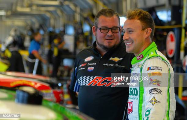 Daniel Hemric driver of the Red Kap/Alsco stands in the garage area during practice for the NASCAR XFINITY Series Alsco 300 at Kentucky Speedway on...