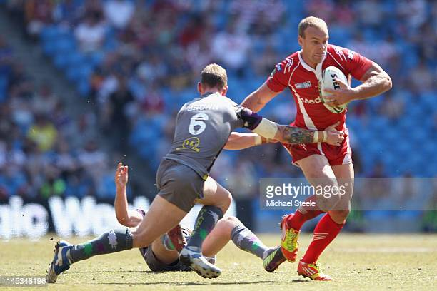Daniel Holdsworth of Salford City Reds holds off Kevin Brown of Huddersfield Giants during the Stobart Super League 'Magic Weekend' match between...