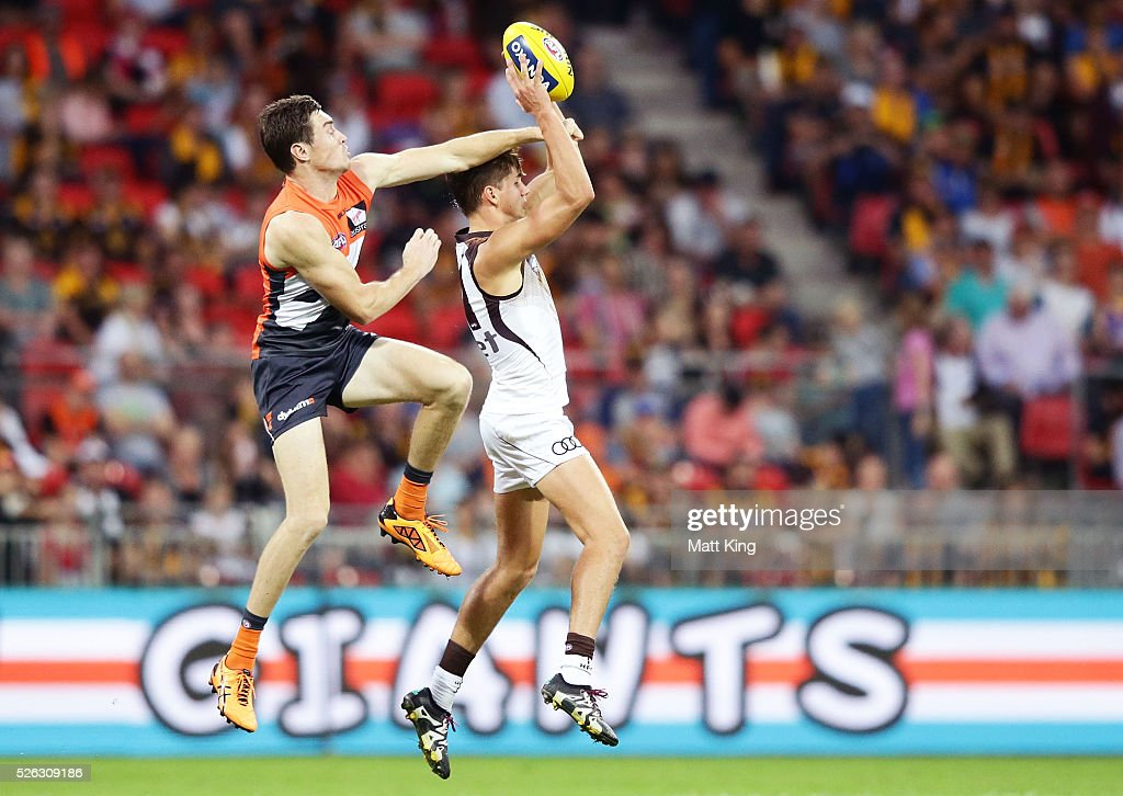 Daniel Howe of the Hawks is challenged by Jeremy Cameron of the Giants during the round six AFL match between the Greater Western Sydney Giants and the Hawthorn Hawks at Spotless Stadium on April 30, 2016 in Sydney, Australia.
