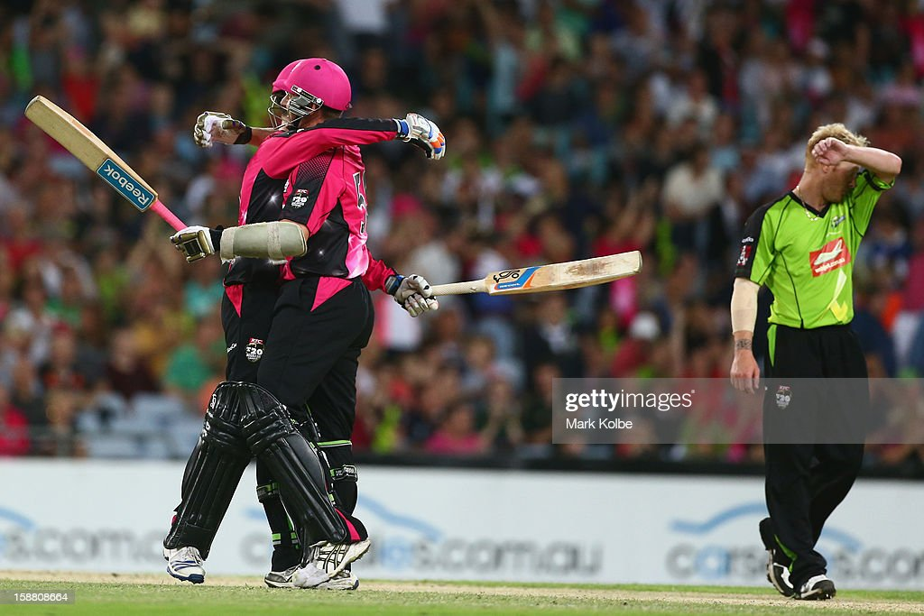 Daniel Hughes and Brett Lee of the Sixers celebrate victory as Scott Coyte of the Thunder looks dejected during the Big Bash League match between Sydney Thunder and the Sydney Sixers at ANZ Stadium on December 30, 2012 in Sydney, Australia.