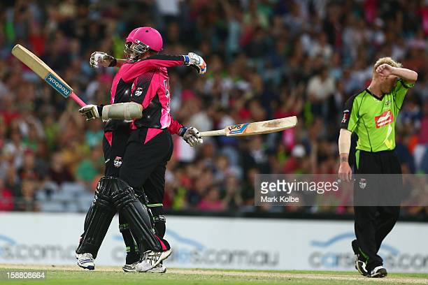 Daniel Hughes and Brett Lee of the Sixers celebrate victory as Scott Coyte of the Thunder looks dejected during the Big Bash League match between...