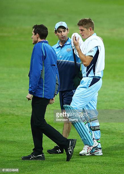 Daniel Hughes of the Blues retires hurt after being struck on the helmet by a short delivery during the Matador BBQs One Day Cup match between New...