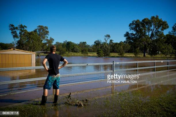 Daniel Jones watches as floodwaters caused by Cyclone Debbie recede in the town of Beenleigh on April 2 2017 Rising floods continued to plague parts...