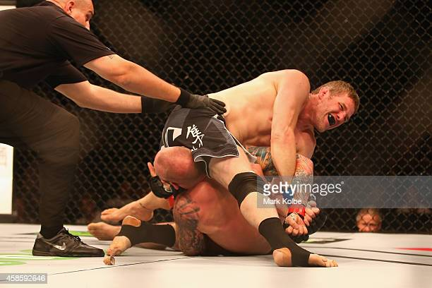 Daniel Kelly of Australia claims victory with an arm bar over Zachrich in their middleweight fight during the UFC Fight Night 55 event at Allphones...