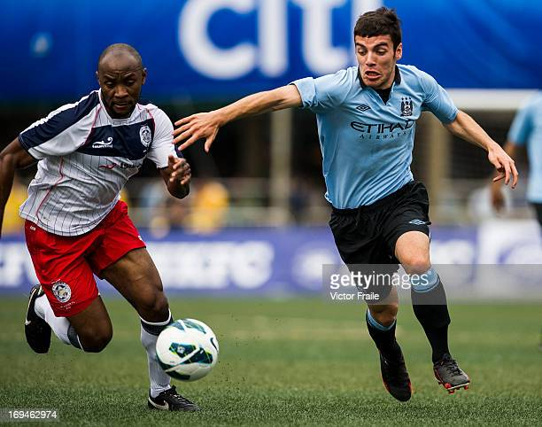 Daniel Lema of Manchester City and Ghislain Bell of Yau Yee League Select fight for the ball on day two of the Hong Kong International Soccer Sevens...