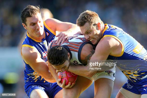 Daniel Lloyd of the Giants gets tackled by Sam Butler and Sam Mitchell of the Eagles during the round 10 AFL match between the West Coast Eagles and...