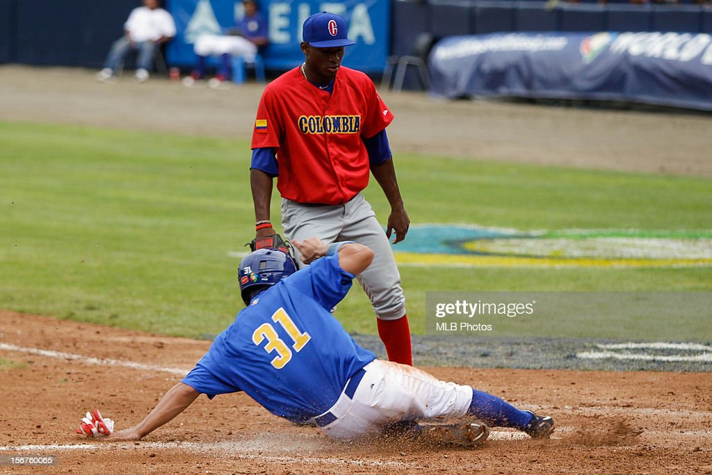 Daniel Matsumoto #31 of Team Brazil scores on a wild pitch as Dewen Perez #12 of Team Colombia looks on in the bottom of the seventh inning during Game 3 of the Qualifying Round of the World Baseball Classic between Team Colombia and Team Brazil at Rod Carew National Stadium on Saturday, November 17, 2012 in Panama City, Panama.