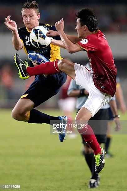 Daniel McBreen of Central Coast challenges Qin Sheng of Guangzhou Evergrande during the AFC Champions League knockout round match between Guangzhou...