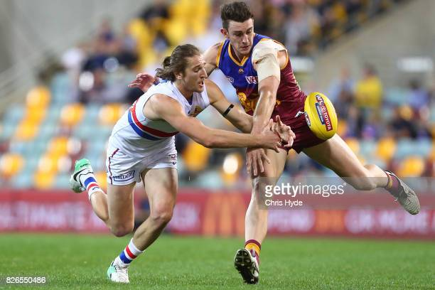 Daniel McStay of the Lions and Marcus Bontempelli of the Bulldogs compete for the ball during the round 20 AFL match between the Brisbane Lions and...