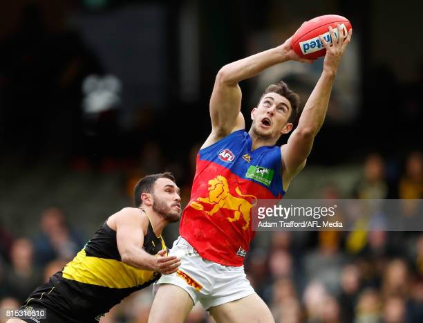 Daniel McStay of the Lions marks the ball over Shane Edwards of the Tigers during the 2017 AFL round 17 match between the Richmond Tigers and the...