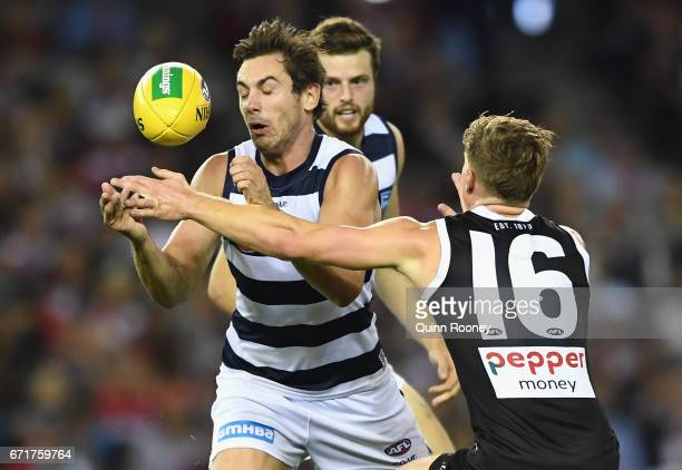Daniel Menzel of the Cats handballs whilst being tackled Jack Newnes of the Saints during the round five AFL match between the St Kilda Saints and...