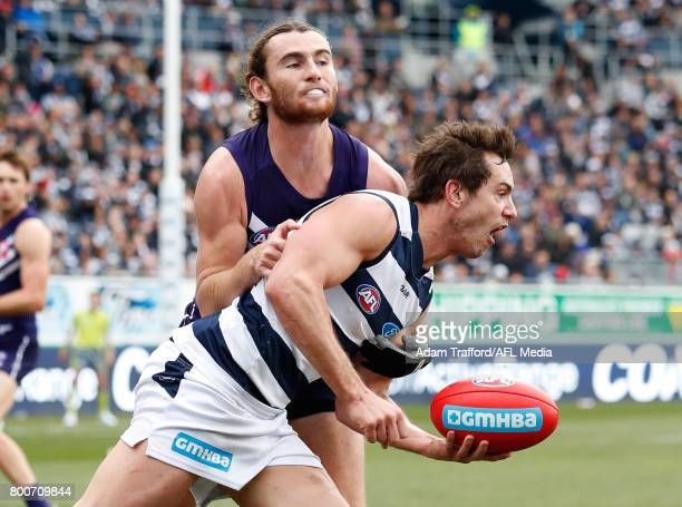 Daniel Menzel of the Cats is tackled by Connor Blakely of the Dockers during the 2017 AFL round 14 match between the Geelong Cats and the Fremantle...