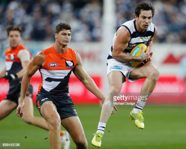 Daniel Menzel of the Cats marks the ball against Jonathon Patton of the Giants during the round 23 AFL match between the Geelong Cats and the Greater...