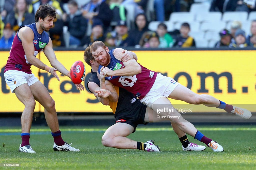 Daniel Merrett of the Lions handballs whilst being tackled by <a gi-track='captionPersonalityLinkClicked' href=/galleries/search?phrase=Jack+Riewoldt&family=editorial&specificpeople=2327975 ng-click='$event.stopPropagation()'>Jack Riewoldt</a> of the Tigers during the round 14 AFL match between the Richmond Tigers and the Brisbane Lions at Melbourne Cricket Ground on June 25, 2016 in Melbourne, Australia.