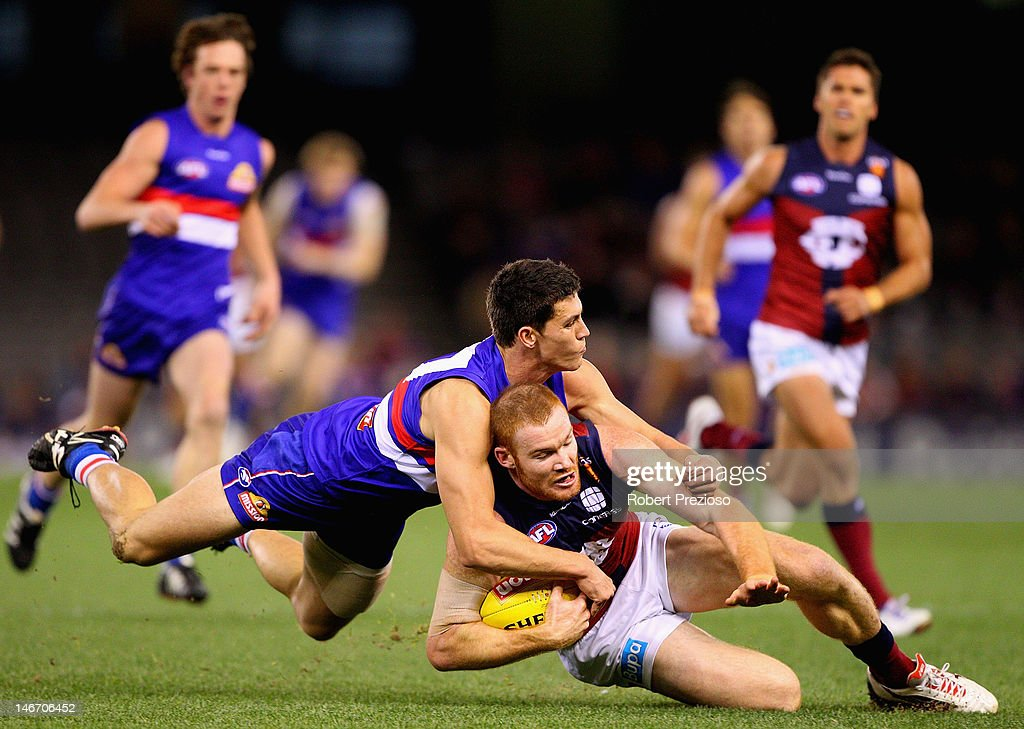 Daniel Merrett of the Lions is tackled during the round 13 AFL match between the Western Bulldogs and the Brisbane Lions at Etihad Stadium on June 23, 2012 in Melbourne, Australia.