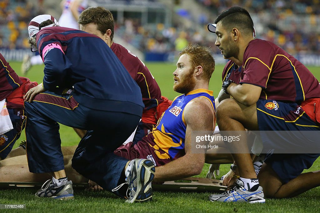 Daniel Merrett of the Lions lays on the stretcher after being injured during the round 22 AFL match between the Brisbane Lions and the Western Bulldogs at The Gabba on August 25, 2013 in Brisbane, Australia.