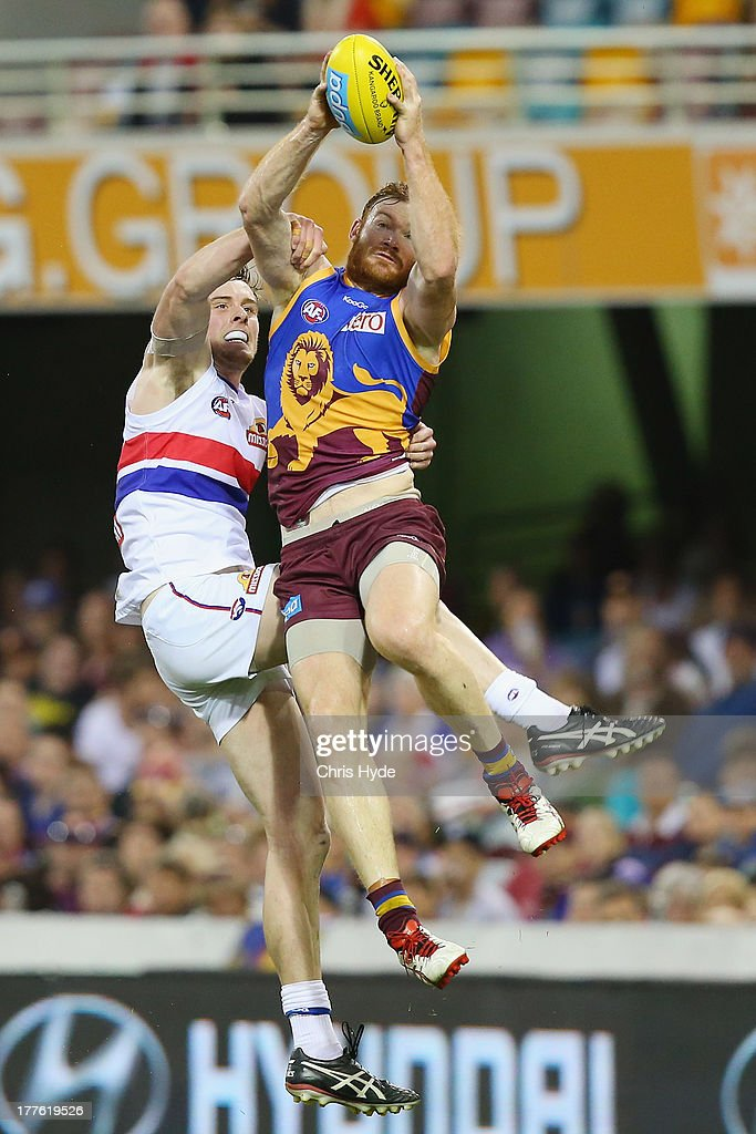 Daniel Merrett of the Lions takes a mark over Jordan Roughhead of the Bulldogs during the round 22 AFL match between the Brisbane Lions and the Western Bulldogs at The Gabba on August 25, 2013 in Brisbane, Australia.