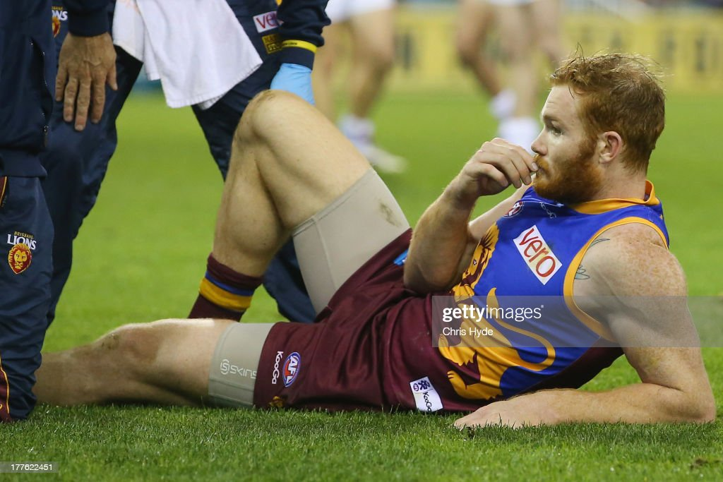 Daniel Merrett of the Lions waits for the stretcher after being injured during the round 22 AFL match between the Brisbane Lions and the Western Bulldogs at The Gabba on August 25, 2013 in Brisbane, Australia.