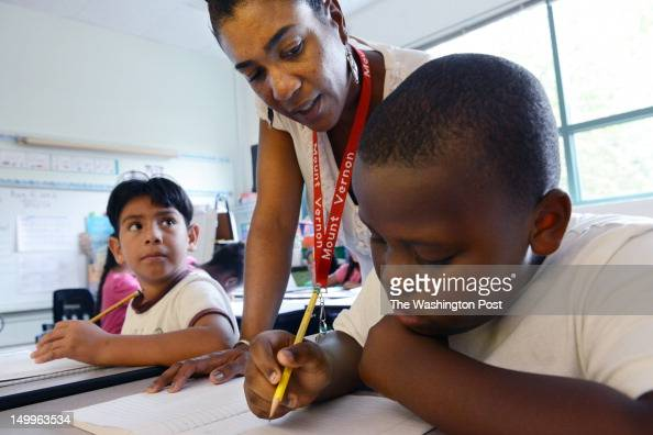 Daniel Montes left looks up at third grade teacher Maria Fletcher center as she helps Elijah Billingsley right on a problem at Mount Vernon Community...