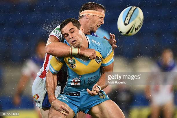 Daniel Mortimer of the Titans is tackled by Kurt Gidley of the Knights during the round three NRL match between the Gold Coast Titans and the...